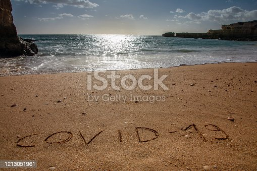 istock Concept of coronavirus holiday, travel and tourism. MERS-Cov. 2019-nCoV. COVID-19 text on the sandy beach, coast and ocean in the background. 1213051961