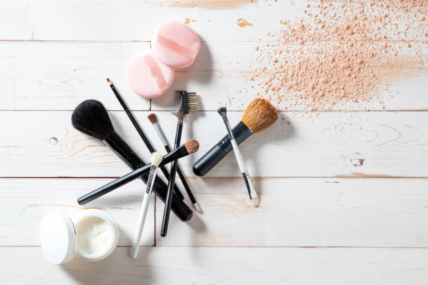 Concept of cosmetics and makeup with powder, skincare and brushes Concept of cosmetics and makeup with free powder, skincare and various professional make up face brushes over white wooden background for elegant beauty background, flat lay view make up brush stock pictures, royalty-free photos & images