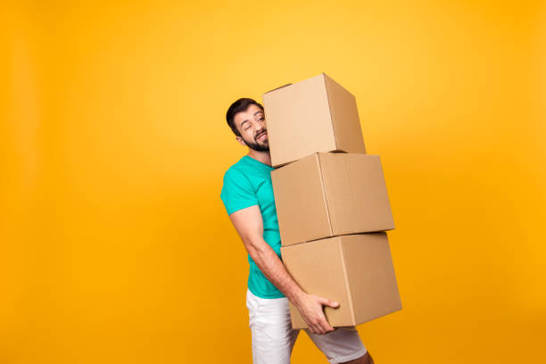 Concept of courier and messenger service. Grimacing handsome guy is trying to keep big stack of cardboard bosex in his hand, isolated on yellow background stock photo