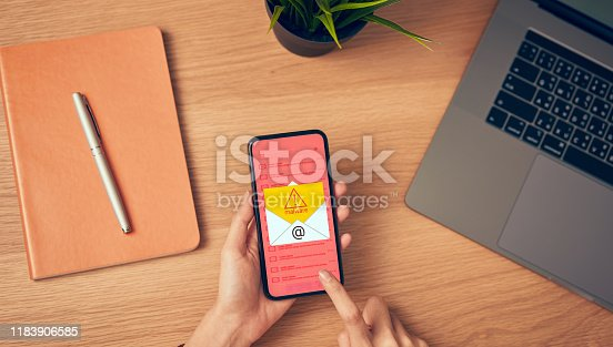 1008108222 istock photo Concept of cyber crime, hand holding smartphone and show malware screen that comes with email, hack password from bank accounts and personal data. 1183906585