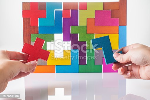 istock Concept of decision making process, logical thinking. Logical tasks. Conundrum, find the missing piece of the proposed. Hand holding wooden puzzle element. Hand sets the last element of the puzzle 897651236