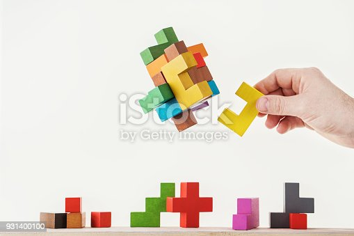 istock Concept of decision making process, logical thinking. Logical tasks. Conundrum, find the missing piece of the proposed. Hand holding wooden puzzle element. 931400100