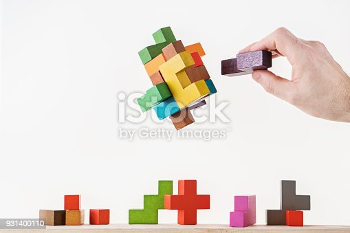 istock Concept of decision making process, logical thinking. Logical tasks. Conundrum, find the missing piece of the proposed. Hand holding wooden puzzle element. 931400110