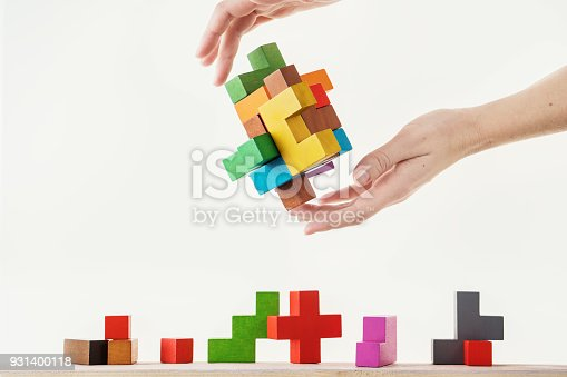 istock Concept of decision making process, logical thinking. Logical tasks. Conundrum, find the missing piece of the proposed. Hand holding wooden puzzle element. 931400118