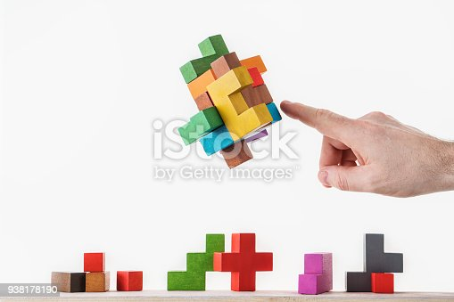 istock Concept of decision making process, logical thinking. Logical tasks. Conundrum, find the missing piece of the proposed. Hand holding wooden puzzle element. 938178190