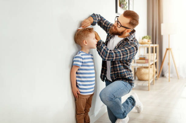 concept van ontwikkeling, opgroeien. vader meet hoogte van zijn jonge kind zoon - lang lengte stockfoto's en -beelden
