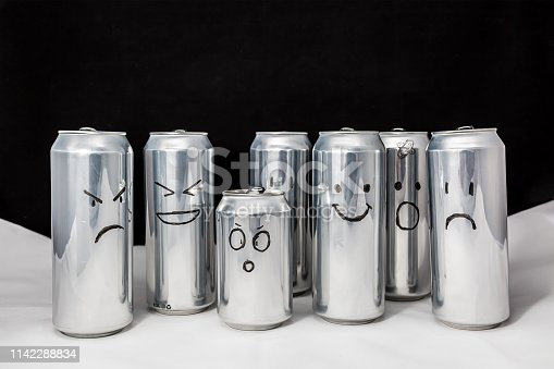Concept of different emotions of diverse people. Emoji on open and empty aluminium cans. Emoticons on black background