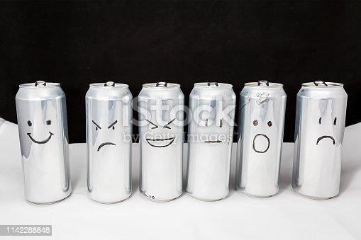 Concept of different emotions of diverse people. Emoji on open and empty aluminium cans. Small can in foreground Emoticons on black background