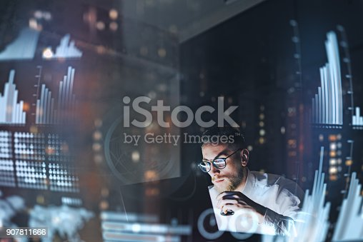 istock Concept of digital diagram,graph interfaces,virtual screen,connections icon.Young finance analist working at modern office.Man using contemporary laptop at night,blurred background.Horizontal. 907811666