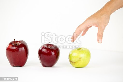 istock Concept of diversity: a woman's hand is about to grab the only green apple among the other red ones 1168913216