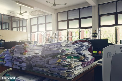 istock Concept of document workload, Pile of unfinished documents on office desk, Stack of business paper, Vintage effect 840729308