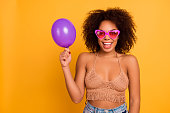istock Concept of ease and simplicity. I'm birthday girl today and waiting for presents! Funny relaxed african in summer outfit woman is showing little ultraviolet air balloon, isolated on yellow background 959608664