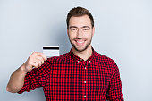 istock Concept of easy using of credit card. Portrait of excited cheerful happy amazed handsome hipster wearing casual clothes is demonstrating plastic credit card, isolated on gray background 966266366
