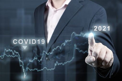 concept of economic recovery after the fall due to the covid 19 coronavirus pandemic. Double exposure of financial graph. Businessman pointing graph corporate future growth plan on dark blue