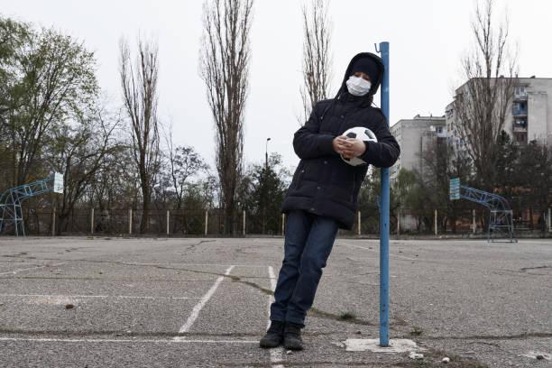 concepto de epidemia y cuarentena - un niño con una máscara facial y una pelota solo en la zona deportiva de la ciudad - foto de stock