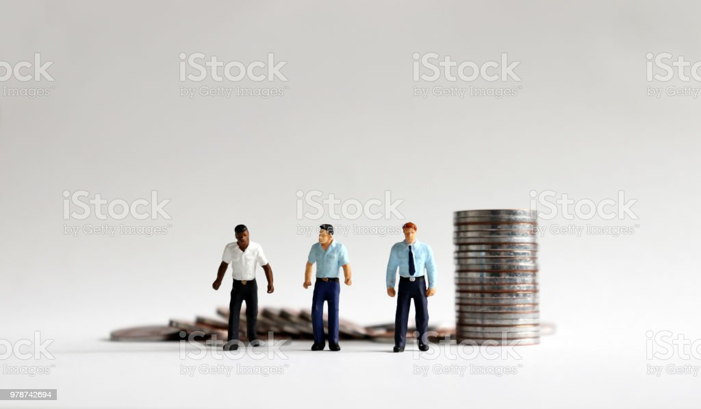 A concept of equal employment conditions. Three miniature men standing with a pile of coins. stock photo