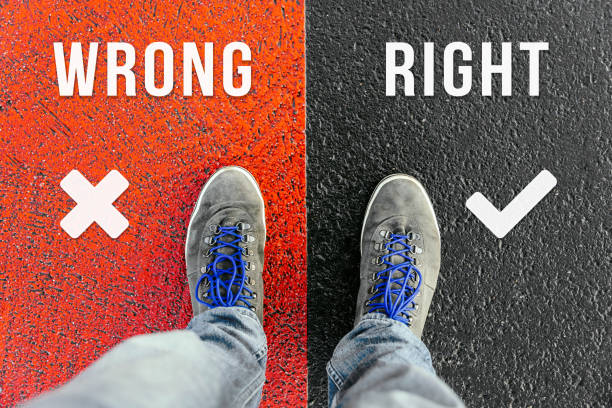 Concept of facing a crucial decision about wrong and right shown by shoes on different colored pathways stock photo