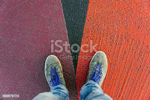 istock Concept of facing a crucial decision shown by shoes on different colored pathways 936879724