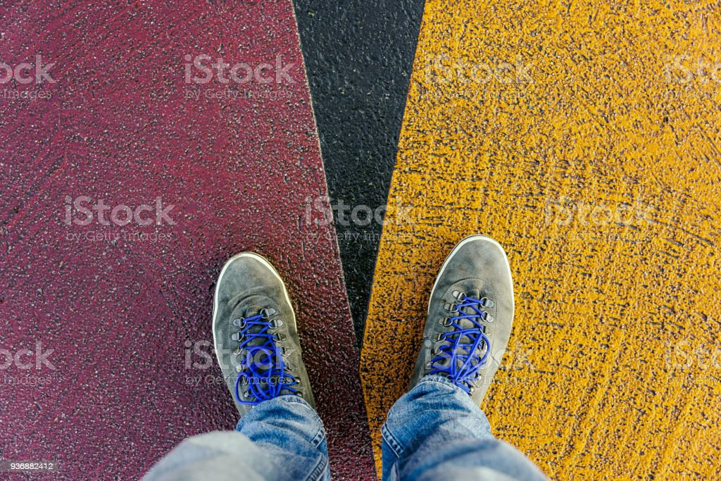 Concept of facing a crucial decision shown by shoes on different colored pathways stock photo