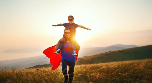 Konzept des Vatertages. Papa und Kind Tochter in Helden-Superhelden-Kostüm bei Sonnenuntergang – Foto