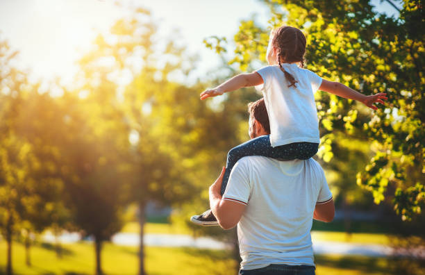 concept of father's day! happy family dad and child daughter back  in nature concept of father's day! happy family dad and child daughter back in   Park in nature genderblend stock pictures, royalty-free photos & images