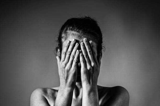 Concept of fear, shame, domestic violence. Concept of fear, shame, domestic violence. Woman covers her face her hands on light  scratched background. Black and white image. aggressively stock pictures, royalty-free photos & images