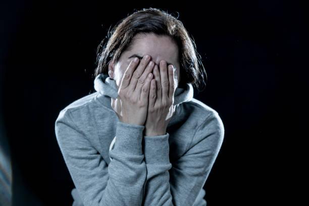 concepto de miedo, vergüenza, violencia y depresión. atractiva latina deprimida mujer cubre su rostro con las manos en un aislado fondo negro - vergüenza fotografías e imágenes de stock