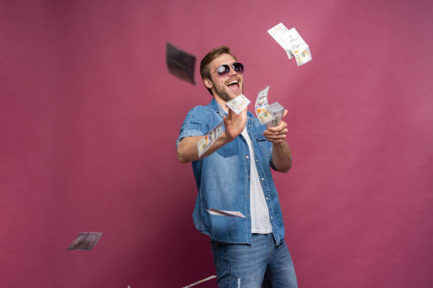 concept of financial wealth, prosperity and lottery winnings - man throwing away his money isolated over pink - throw money away stock pictures, royalty-free photos & images