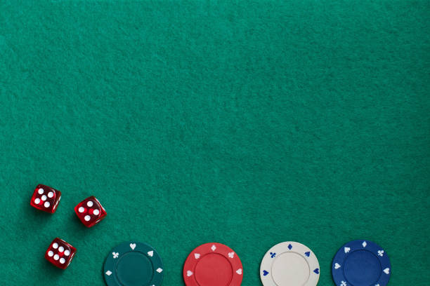 Concept of gambling in casino, sports poker. Gaming dice and colored gaming chips on green gaming table. stock photo