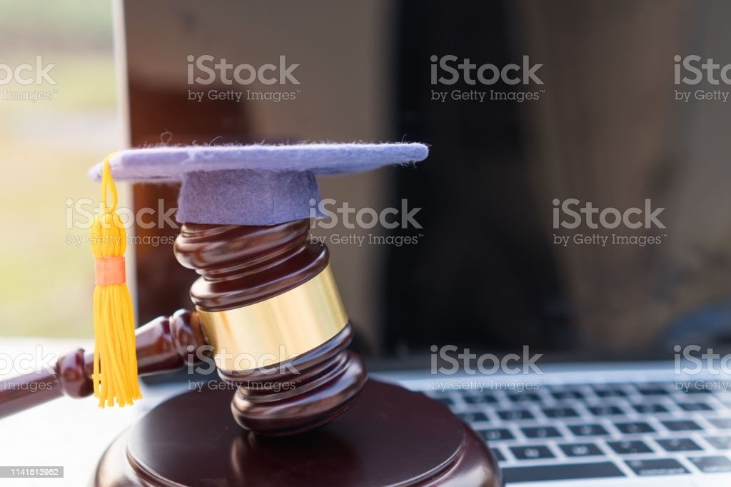 Concept of graduate online study international abroad about jurisprudence laws certificate in university distance education for learning. Graduation diploma hat / Judge gavel on computer notebook. stock photo