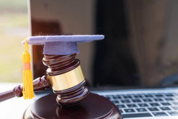 大学遠隔教育における法学法証明書に関する海外留学の考え方卒業証書の帽子/裁判官小槌をコンピュータのノートに。 - パラリーガル ストックフォトと画像