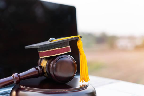大学院オンライン留学のコンセプトについて大学の法学に関する法律の証明コンピュータノートの卒業証書帽子/裁判官早とちり。 - パラリーガル ストックフォトと画像