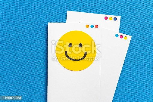 istock Concept of happy work, well-being, well done, feedback, employee recognition award. Paper white notes with yellow circle happy smiling face cartoon illustrated on blue texture background. 1166522953