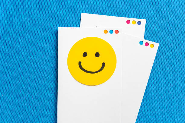 concept of happy work, well-being, well done, feedback, employee recognition award. paper white notes with yellow circle happy smiling face cartoon illustrated on blue texture background. - buona notizia foto e immagini stock