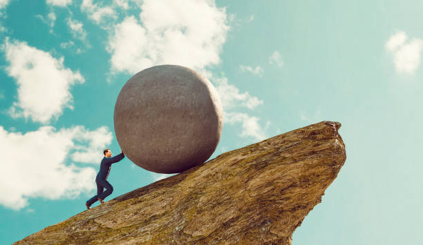 Concept of hard work for businessman pushing rock up a hill stock photo