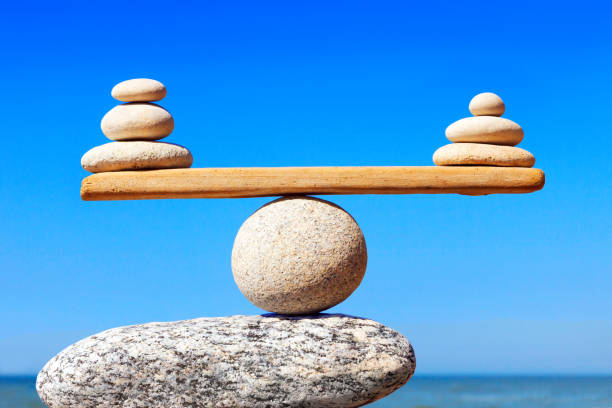 Concept of harmony and balance. Balance stones against the sea. Symbolic scales of stones on the background of the sea and blue sky. Concept of harmony and balance. Pros and cons concept balance stock pictures, royalty-free photos & images