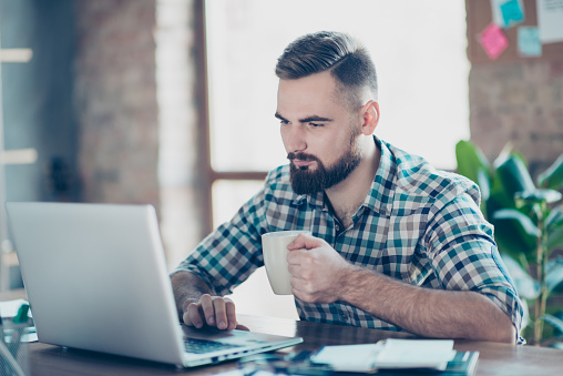 Concept of having a break at work. Concentrated calm peaceful serious office worker  watching carefully a video on the internet using his laptop and drinking tea