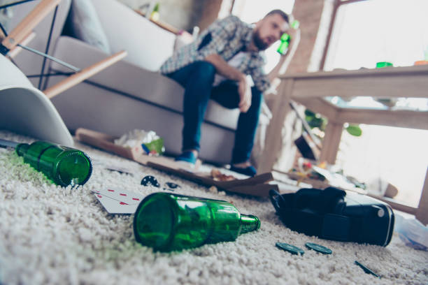 Concept of having headache after global party. Close up low-angle photo of empty green transparent beer bottles lying on nappy beige carpet, guy with nausea sitting on sofa in ob blurred background Concept of having headache after global party. Close up low-angle photo of empty green transparent beer bottles lying on nappy beige carpet, guy with nausea sitting on sofa in ob blurred background bachelor stock pictures, royalty-free photos & images
