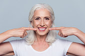 Concept of having strong healthy straight white teeth at old age. Close up portrait of happy with beaming smile female pensioner pointing on her perfect clear white teeth, isolated on gray background