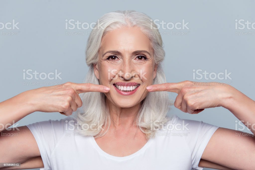 Concept of having strong healthy straight white teeth at old age. Close up portrait of happy with beaming smile female pensioner pointing on her perfect clear white teeth, isolated on gray background stock photo