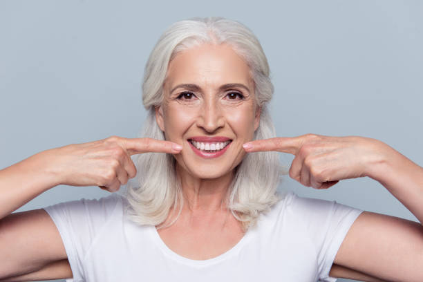 concept of having strong healthy straight white teeth at old age. close up portrait of happy with beaming smile female pensioner pointing on her perfect clear white teeth, isolated on gray background - dental implants stock photos and pictures