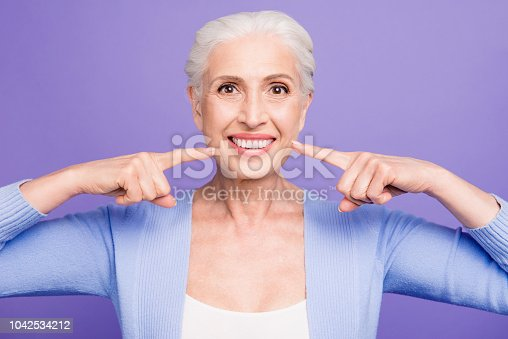 istock Concept of having strong healthy white perfect teeth at old age. Portrait of old lady with beaming smile pointing on her teeth, isolated over violet background 1042534212