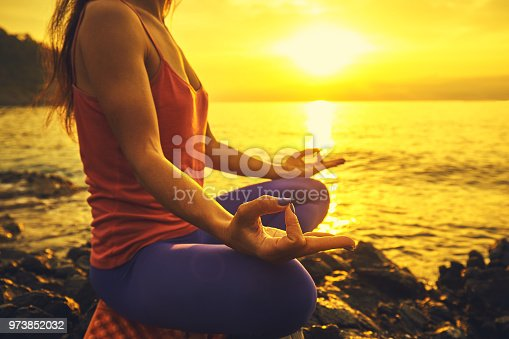 Yoga concept. hand woman practicing lotus pose on beach