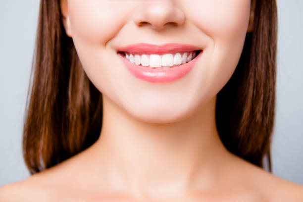 concept of healthy wide beautiful smile. cropped close up photo of healthy without caries shiny toothy woman's smile, isolated on grey background - dental implants stock photos and pictures