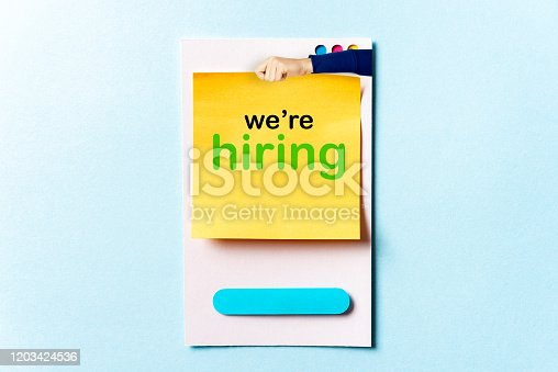 477419728istockphoto Concept of Help wanted sign. Woman hand holding a sticky note with we're hiring words concept on paper card and blue background with space for text. 1203424536