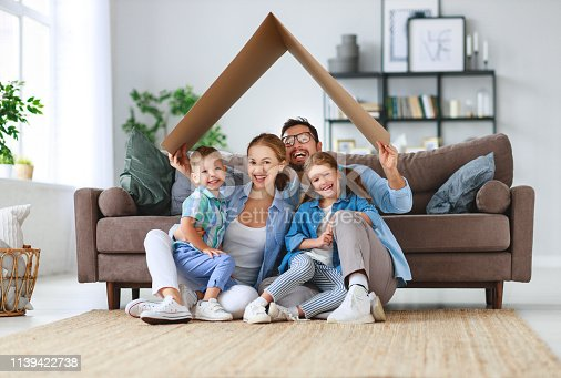 istock concept of housing and relocation. happy family mother father and kids with roof at home 1139422738