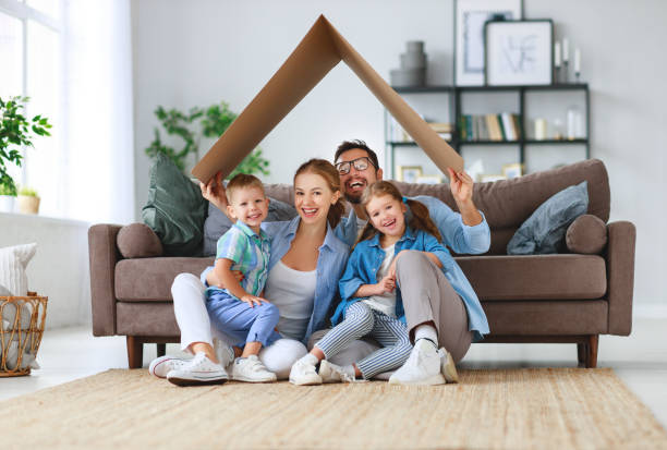 concept of housing and relocation. happy family mother father and kids with roof at home - house imagens e fotografias de stock