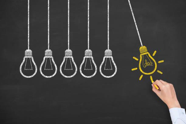 concept of idea and innovation with light bulb on blackboard - explorer de nouveaux territoires photos et images de collection