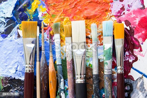istock Concept of Individuality, Various Paintbrushes on a Palette 693028060