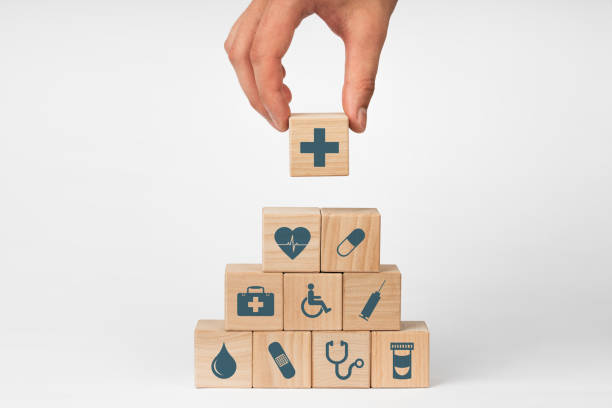 Concept of Insurance for your health, Hand hold wooden block with icon healthcare medical stock photo